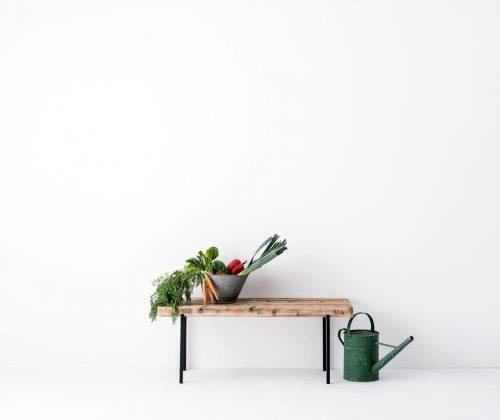 Sitzbank Altholz 01 von weld & co in Größe M, inszeniert mit Waagschale, Gemüse und Gießkanne.