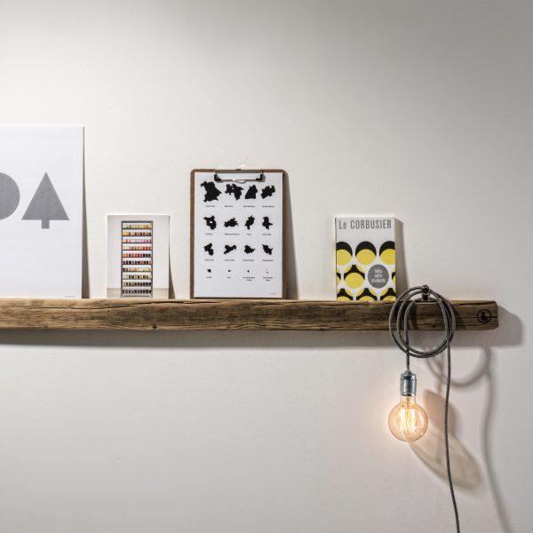 Bilderleiste Altholz 01 von weld & co in Größe L, inszeniert mit grafischen Prints von Elena Perschin und einer Retro-Leuchte.
